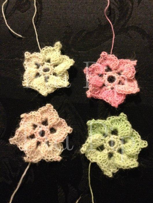 Blomster lavet af samme garn som sjalet og overvejer at bruge dem på det.