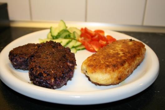 Rødkålsfrikadeller serveret med kartoffelmosfritte med svampefyld og lidt grønt på siden.